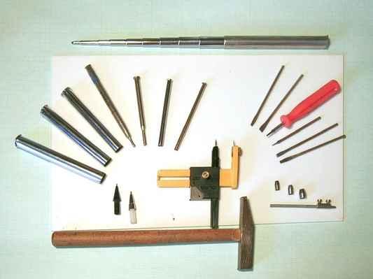 obr. č.31 - Pomůcky a nástroje k tvorbě otvorů - z leva nahoru: tři průměry dílů anténky, tři různé kovové náplně do propisovačky, ploché sekáčky ze špic kol motocyklu, kulaté vyměnitelné vytínače na kůži, řezací kružítko Olfa, trubičky z mikrotužky. Nahoře nerozdělaná vysouvací anténka z tranzistorového rádia.