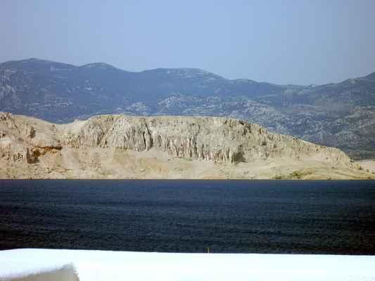 Pohled přes Paški zaliv k Pašským vratům, v pozadí pohoří Velebit